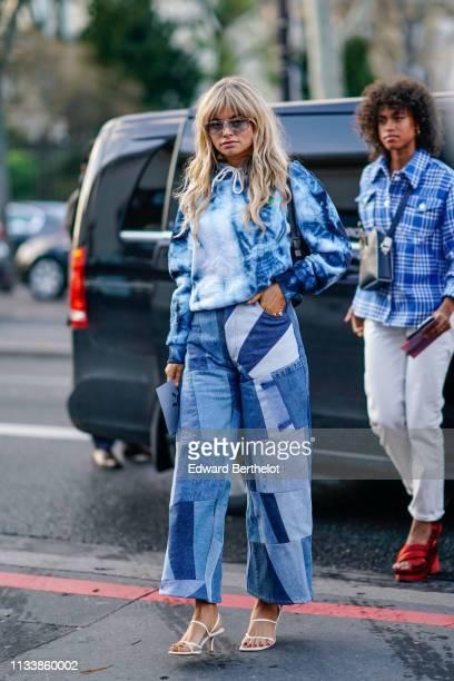 Claire Rose Cliteur wears sunglasses a blue tieanddye top blue patchwork flare jeans white sandals outside Shiatzy Chen during Paris Fashion Week...
