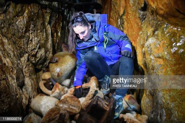 Claire Simonin president of the French association Ar Viltansou searches in a partially submerged cave only accessible at low tide where a container...