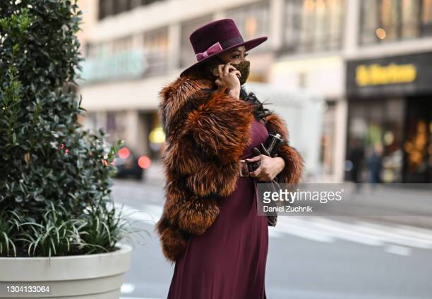Claire Summers is seen wearing a faux fur coat and maroon dress and hat outside the Christian Siriano show during New York Fashion Week F/W21 on...