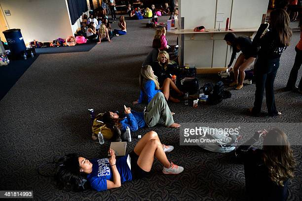 Claire Vonnieda of Montana and Gioia Bartalo of Florida play on their phones during tryouts for the 20142015 Denver Broncos cheerleaders More than...