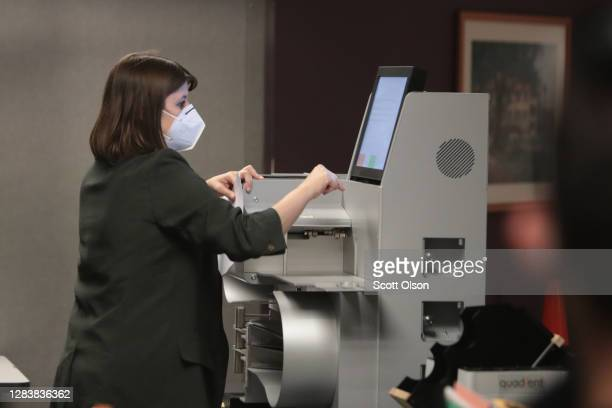 Claire Woodall-Vogg, executive director of the Milwaukee election commission collects the count from absentee ballots from a voting machine on...