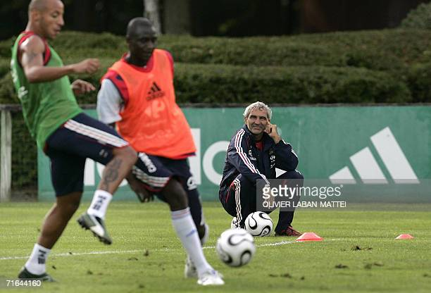 France's coach Raymond Domenech looks at his player midfielder Julien Faubert during a training session 14 August 2006 in Clairfontaine two days...