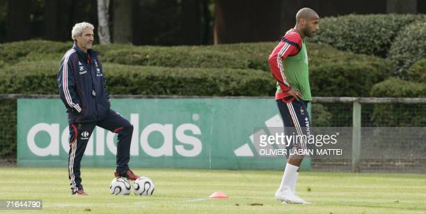 France's coach Raymond Domenech looks at forward Thierry Henry playing during a training session 14 August 2006 in Clairfontaine two days before the...