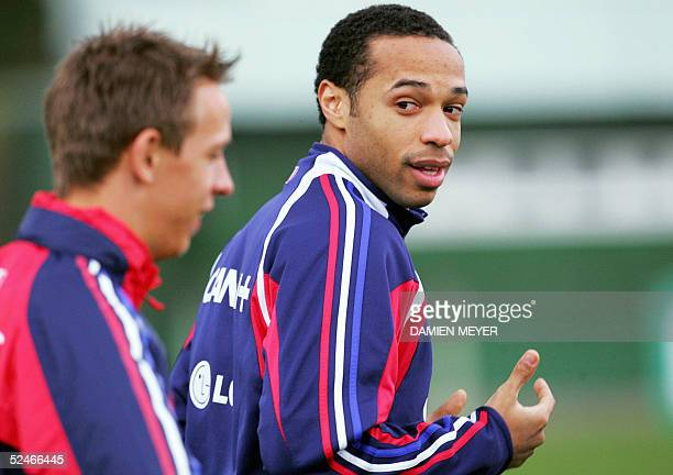 Clairefontaine-en-Yvelines, FRANCE: French football national team forward Thierry Henry chats with his teammate Benoit Pedretti during a training...