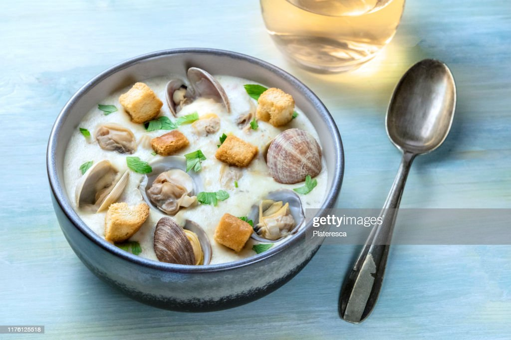 Clam chowder, decorated with fresh parsley and croutons, on a blue background, with a glass of white wine and a spoon : Stock Photo