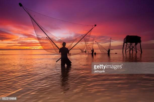 Clam harvesting - Fisherman at sunrise at Tan Thanh Beach - Go Cong