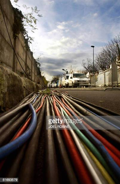 Cables are displayed on the road to bring electricity to the media caravans parked in the street of the Percy military hospital in the Paris...