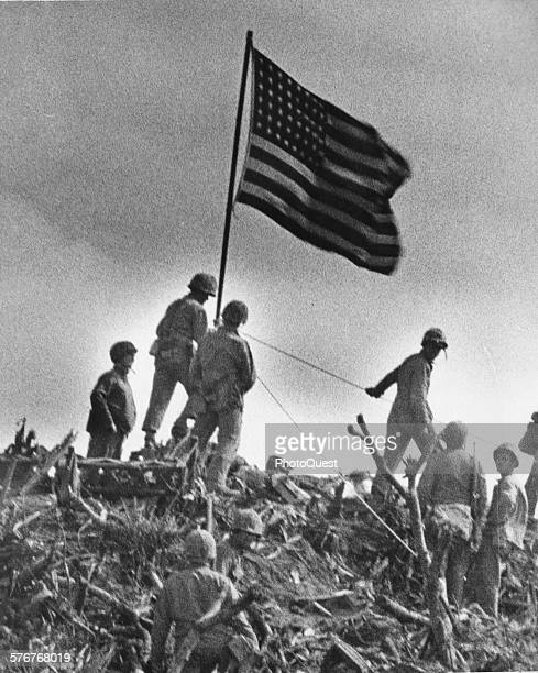Clambering up the lavaencrusted walls of Mount Suribachi a Coast Guard combat photographer snapped this shot of Old Glory unfurled to the breeze a...
