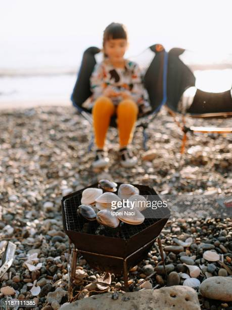 clams being grilled on bbq on beach with child in background - simple living stock pictures, royalty-free photos & images