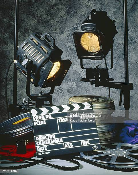 clapper board with headlights and film reels - spotlight film stock photos and pictures