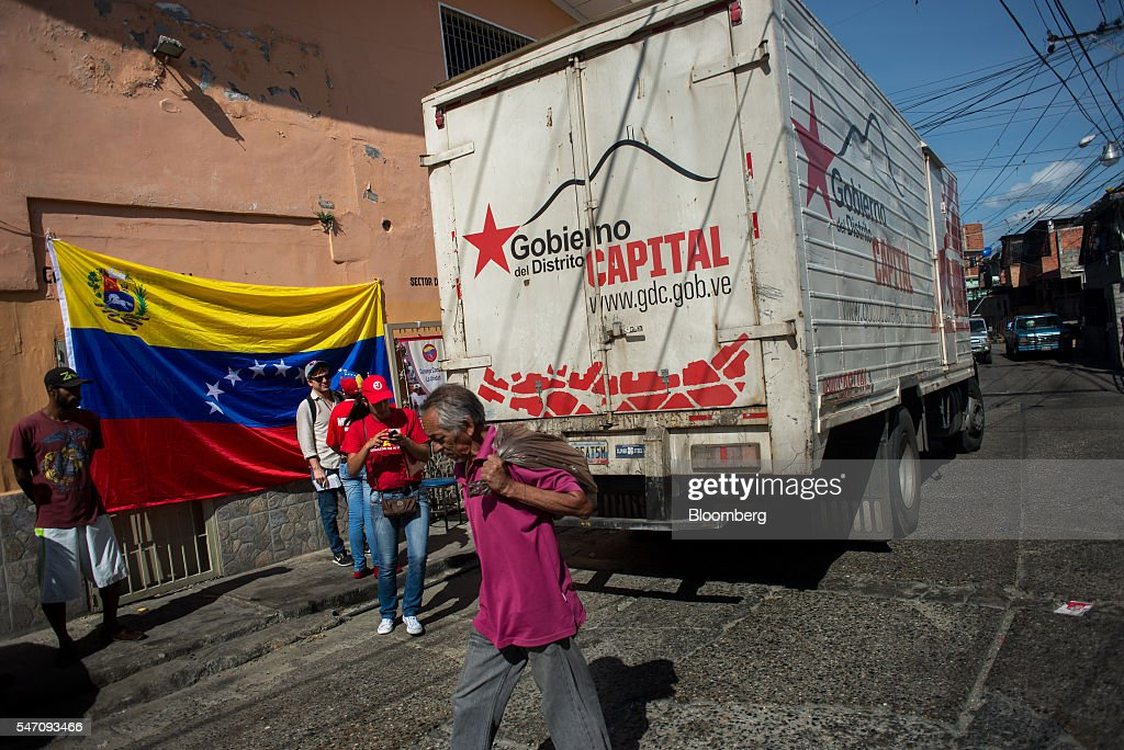 CLAPs members stand next to a truck loaded with groceries from the government in the Catia neighborhood on the outskirts of Caracas, Venezuela, on Saturday, July 2, 2016. In an attempt to regain control, President Nicolas Maduro has tapped loyal neighborhood groups, called Local Committees for Supply and Production (CLAPs), and put them in charge of distributing as much as 70 percent of the nation's food. Photographer: Manaure Quintero/Bloomberg via Getty Images
