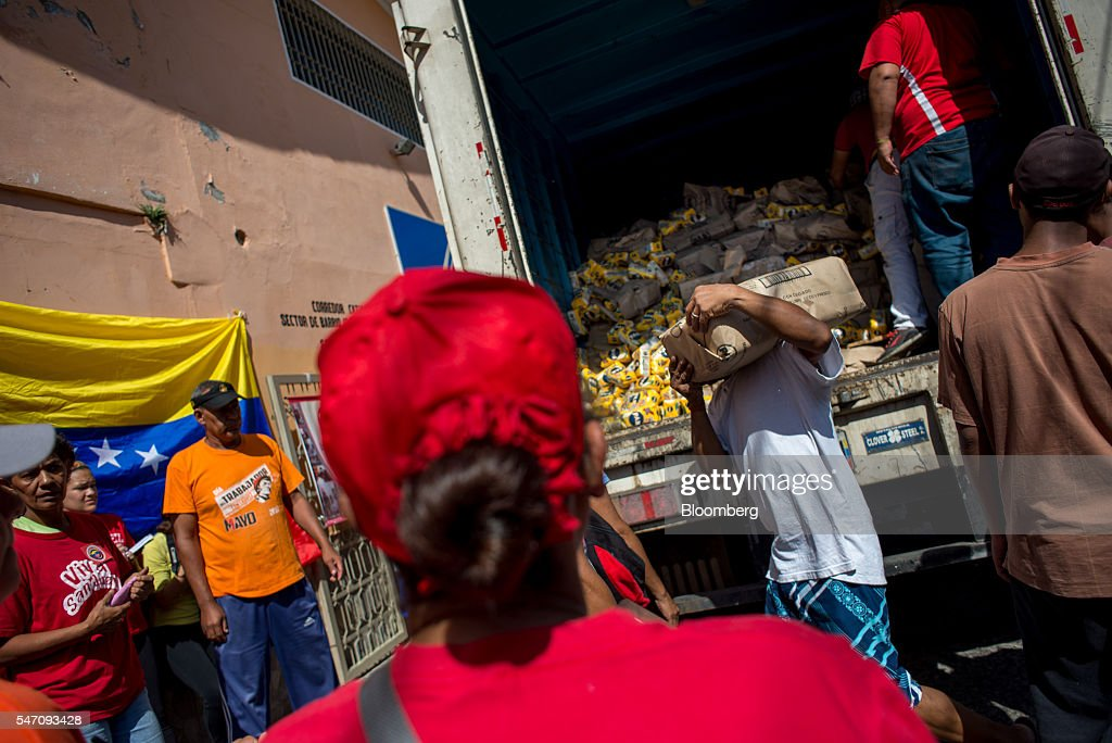 CLAPs members unload a truck of groceries in the Catia neighborhood on the outskirts of Caracas, Venezuela, on Saturday, July 2, 2016. In an attempt to regain control, President Nicolas Maduro has tapped loyal neighborhood groups, called Local Committees for Supply and Production (CLAPs), and put them in charge of distributing as much as 70 percent of the nation's food. Photographer: Manaure Quintero/Bloomberg via Getty Images