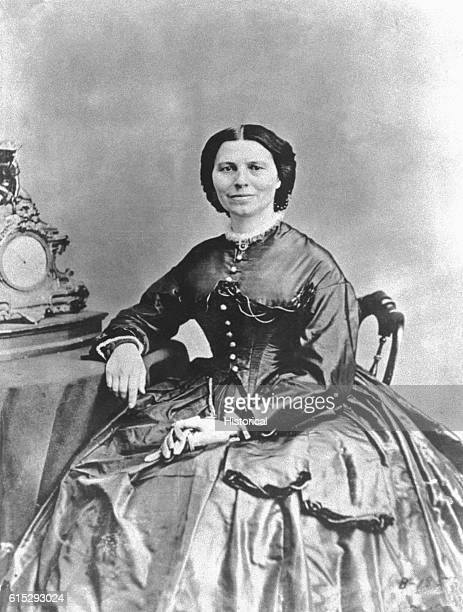 Clara Barton under President Abraham Lincoln's charge for sending supplies to civil war soldiers holds a pair of gloves next to a table and clock