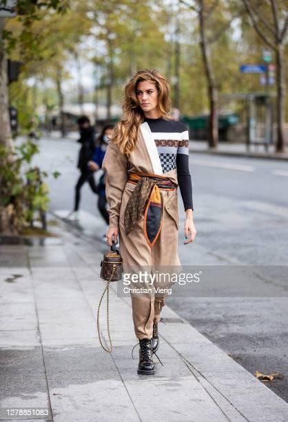 Clara Berry is seen wearing beige pants and jacket, Louis Vuitton bag, top outside Louis Vuitton during Paris Fashion Week - Womenswear Spring Summer...