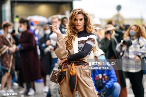 Clara Berry wears a beige Vuitton jacket, a black and brown striped monogram print and checkered pullover, beige pants, a Vuitton scarf around the...