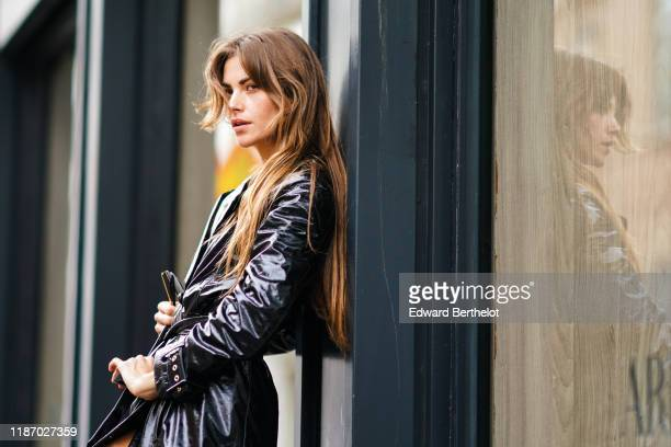 Clara Berry wears a black shiny trench coat outside the Blumarine show during Milan Fashion Week Spring/Summer 2020 on September 20 2019 in Milan...