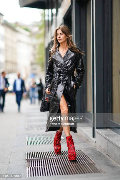 Clara Berry wears a black shiny trench coat red cow pattern boots outside the Blumarine show during Milan Fashion Week Spring/Summer 2020 on...