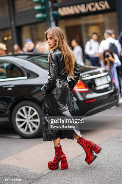 Clara Berry wears a shiny black leather trench coat red and black leopard print platform Nakedwolfe ankleboots a black woven beadwork handbag outside...