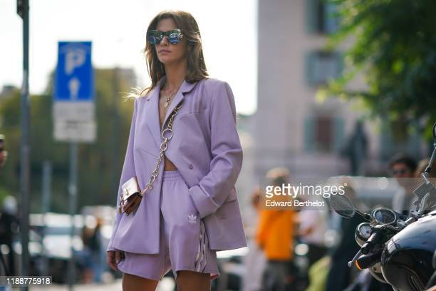 Clara Berry wears mirrored sunglasses a necklace a brown crossbody bag a light mauve oversized jacket light mauve Adidas shorts with stripes on the...