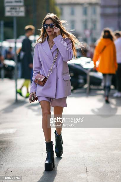 Clara Berry wears mirrored sunglasses, a necklace, a brown crossbody bag, a light mauve oversized jacket, light mauve Adidas shorts with stripes on...