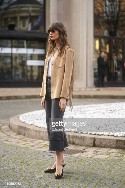 Clara Luciani wears sunglasses a brown fringed jacket a white top cropped pants pointy shoes outside Miu Miu during Paris Fashion Week Womenswear...