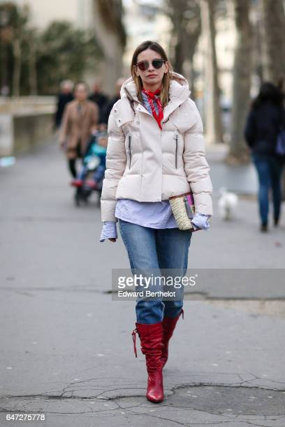 Clara Racz wears a white puffer coat a striped shirt blue denim jeans pants and red boots outside the Paco Rabanne show during Paris Fashion Week...