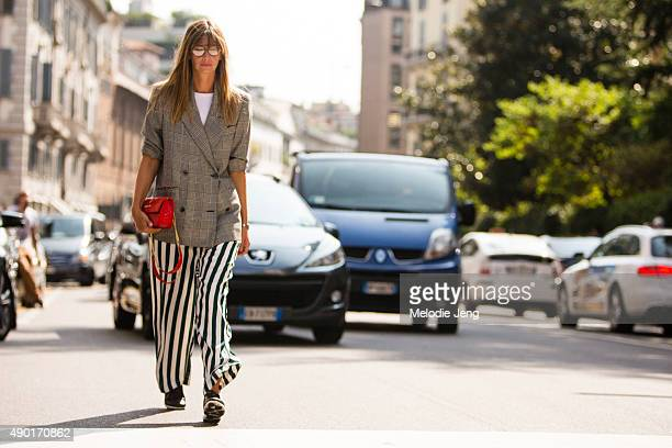 Clara Racz wears glasses a houndstooth doublebreasted jacket loose striped pants and a red purse during the Milan Fashion Week Spring/Summer 16 on...