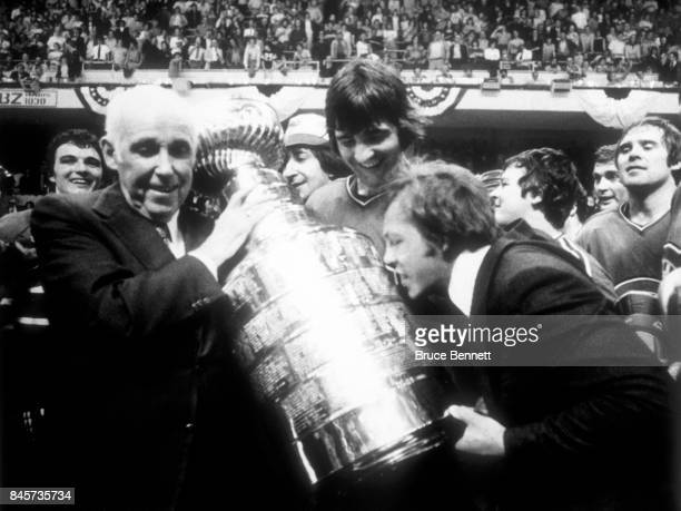 Clarance Campbell gets ready to hand the Stanley Cup Trophy to Serge Savard and Yvan Cournoyer of the Montreal Candiens after the Candiens defeated...