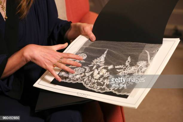 Clare Waight Keller designer at Givenchy holds lace as she gives an interview the day after the Duchess of Sussex walked down the aisle of St...