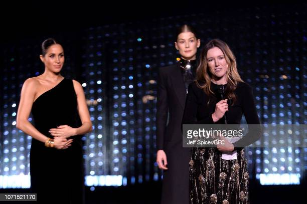 Clare Waight Keller is watched by Meghan Duchess of Sussex and Rosamund Pike as she speaks on stage after receiving the award for British Designer of...