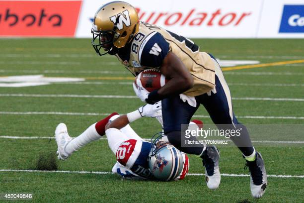 Clarence Denmark of the Winnipeg Blue Bombers dodges a tackle by Geoff Tisdale of the Montreal Alouettes during the CFL game at Percival Molson...
