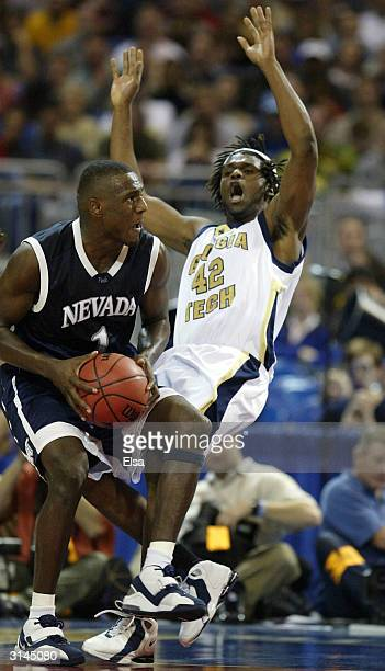 Clarence Moore of the Georgia Tech Yellow Jackets falls back as Kirk Snyder of the Nevada Wolfpack runs into him during the third round game of the...