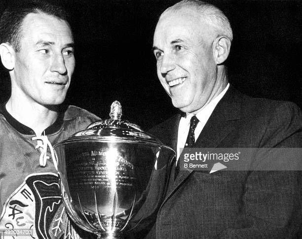 Clarence S Campbell hands out the James Norris Memorial Trophy to Pierre Pilote of the Chicago Blackhawks circa 1963 in Chicago Illinois