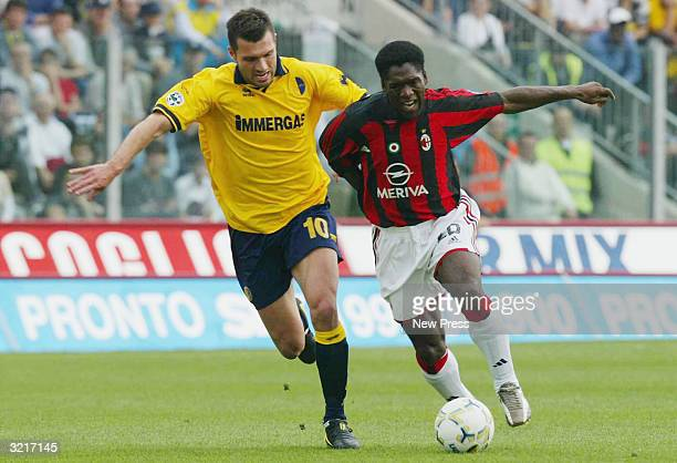 Clarence Seedorf of AC Milan tries to get past Modena's Nicola Corrent during the Serie A match between AC Milan and Modena at Modena's Alberto...