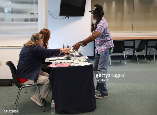 Clarence Singleton registers to vote with Rosey Brockamp and Sheryl Podley who are voter registration workers at the Lee Country Supervisor of...