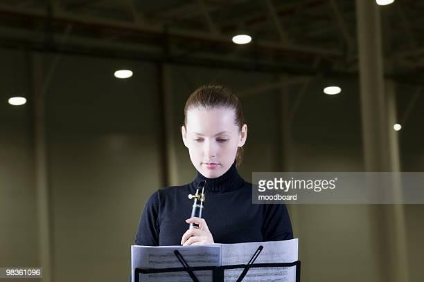 clarinet player stands with sheet music under spotlights - clarinete fotografías e imágenes de stock