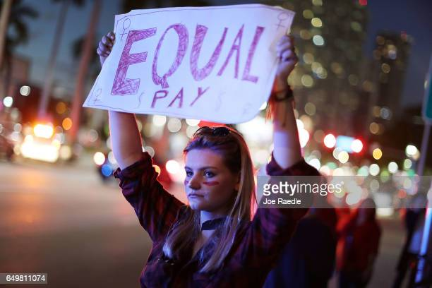 Clarissa Horsfall holds a sign reading 'Equal Pay' as she joins with others during 'A Day Without A Woman' demonstration on March 8 2017 in Miami...