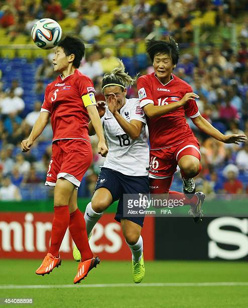 Clarisse Le Bihan of France jumps for a header with Choe Sol Gyong and Ri Un Yong of Korea DPR during the FIFA U20 Women's World Cup Canada 2014 3rd...