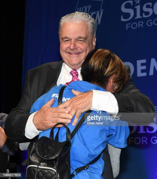 Clark County Commission Chairman and Democratic gubernatorial candidate Steve Sisolak hugs a supporter who jumped onstage after Sisolak won his race...