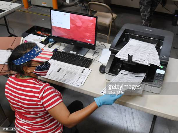 Clark County election worker scans mail-in ballots at the Clark County Election Department on October 20, 2020 in North Las Vegas, Nevada. In-person...