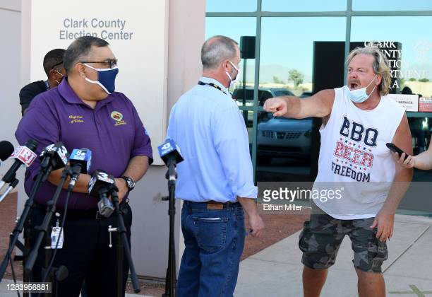 Clark County public information officer Dan Kulin steps in front of a protester as he interrupts a news conference to discuss ballot counting by...