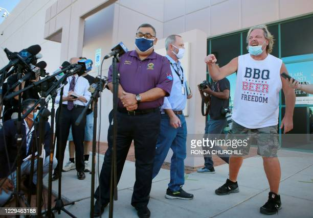 Clark County Registrar of Voters Joe Gloria, left, is interrupted by a disgruntled member of the public during a press conference outside Clark...