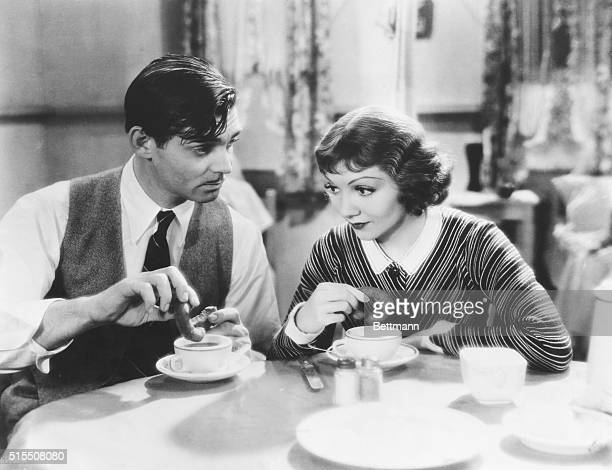 Clark Gable and Claudette Colbert having some coffee and donuts in a scene from the movie It Happened One Night