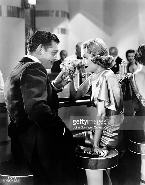 Clark Gable and Constance Bennett toast in a scene from the 1935 film After Office Hours