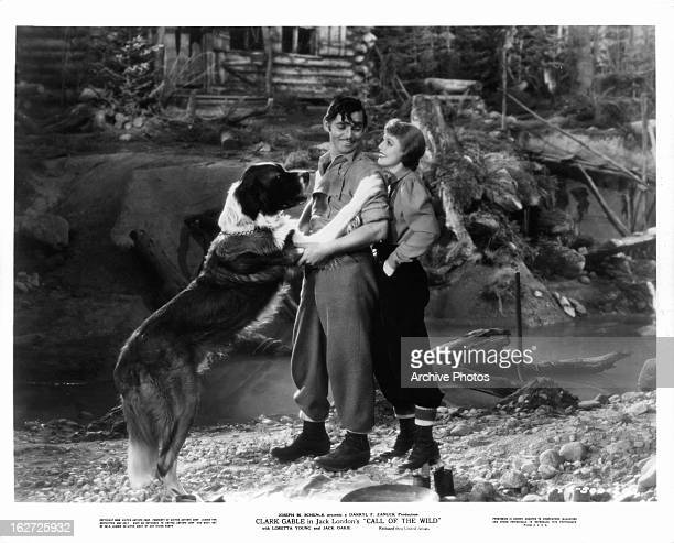 Clark Gable and Loretta Young out in the woods with big dog in a scene from the film 'The Call Of The Wild' 1935