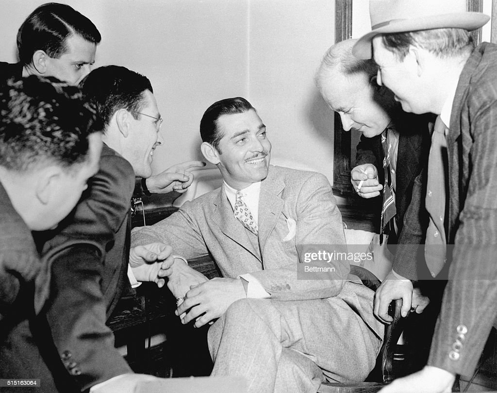 Clark Gable and newspaper reporters are shown in a mutually enjoyable interview during recess in Los Angeles Court, April 23, 1937, at the trial of Mrs.Violet Wells Norton, an Englishwoman accused of mail in fraud and charging Gable with being the father of her child.