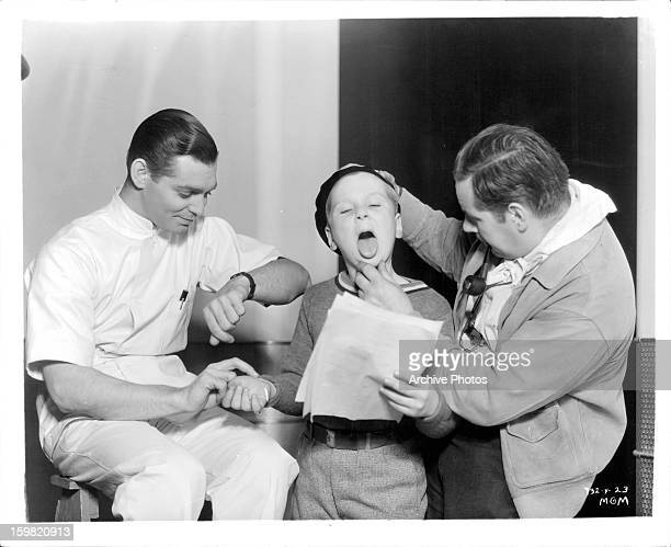 Clark Gable checking pulse of child in a scene from the film 'Men In White' 1934