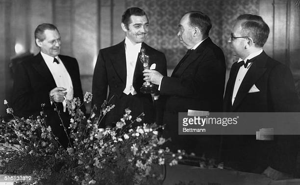 Clark Gable is shown being presented a gold statuette by Irvin S Cobb noted writer for his acting in It Happened One Night the Columbia film which...