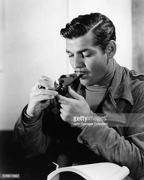 Clark Gable lights his pipe while reading over the script for San Francisco a romantic drama directed by WS Van Dyke