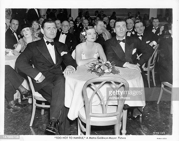 Clark Gable Myrna Loy and Walter Pidgeon seated and all looking forward from table at formal event in a scene from the film 'Too Hot To Handle' 1938